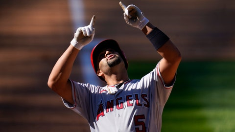 Los Angeles Angels' Albert Pujols gestures as he crosses home plate after hitting a two-run home run of Colorado Rockies relief pitcher Carlos Estevez in the eighth inning of a baseball game Sunday, Sept. 13, 2020, in Denver. (AP Photo/David Zalubowski)