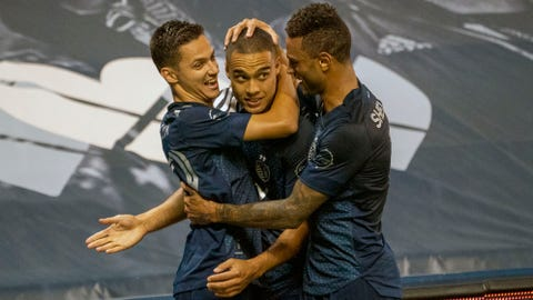 Oct 7, 2020; Kansas City, Kansas, USA; Sporting Kansas City defender Winston Reid (middle) celebrates with midfielder Ilie Sanchez (left) and forward Khiry Shelton (11) after scoring against the Chicago Fire during the second half at Children's Mercy Park. Mandatory Credit: Denny Medley-USA TODAY Sports
