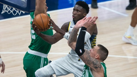 Dec 29, 2020; Indianapolis, Indiana, USA; Indiana Pacers guard Victor Oladipo (4) shoots the ball while Boston Celtics center Daniel Theis (27) defends in the third quarter at Bankers Life Fieldhouse. Mandatory Credit: Trevor Ruszkowski-USA TODAY Sports