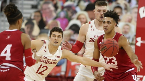 Jan 7, 2021; Madison, Wisconsin, USA; Wisconsin Badgers guard Trevor Anderson (12) attempts to intercept a pass to Indiana Hoosiers forward Trayce Jackson-Davis (23) during the first half at the Kohl Center. Mandatory Credit: Mary Langenfeld-USA TODAY Sports