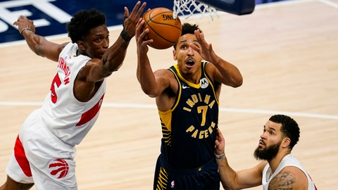 Indiana Pacers guard Malcolm Brogdon (7) shoots between Toronto Raptors forward Stanley Johnson (5) and guard Fred VanVleet (23) during the first half of an NBA basketball game in Indianapolis, Monday, Jan. 25, 2021. (AP Photo/Michael Conroy)