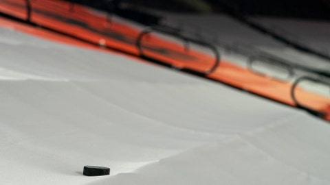 A puck lays on the tarp coving the seats prior to the first period of an NHL hockey game between the Pittsburgh Penguins and the Philadelphia Flyers, Wednesday, Jan. 13, 2021, in Philadelphia. (AP Photo/Chris Szagola)