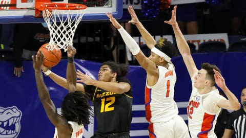 Missouri Tigers guard Dru Smith (12) goes up and under the basket to score the game winning basket against three Florida defenders in the final seconds during a game against the Florida Gators at the Exactech Arena in Gainesville March 3, 2020.  UFvs.Missouri16