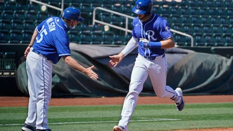 Kansas City Royals' Hunter Dozier, right, celebrates with third base coach Vance Wilson, left, after hitting a home run in the first inning of a spring training baseball game against the Oakland Athletics, Monday, March 8, 2021, in Surprise, Ariz. (AP Photo/Sue Ogrocki)