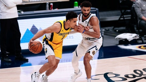 Mar 15, 2021; Denver, Colorado, USA; Indiana Pacers guard Malcolm Brogdon (7) controls the ball as Denver Nuggets guard Jamal Murray (27) guards in the second quarter at Ball Arena. Mandatory Credit: Isaiah J. Downing-USA TODAY Sports