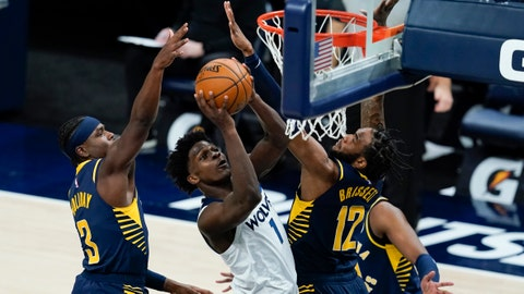 Minnesota Timberwolves' Anthony Edwards (1) puts up a shot against Indiana Pacers' Aaron Holiday and Oshae Brissett (12) during the first half of an NBA basketball game, Wednesday, April 7, 2021, in Indianapolis. (AP Photo/Darron Cummings)
