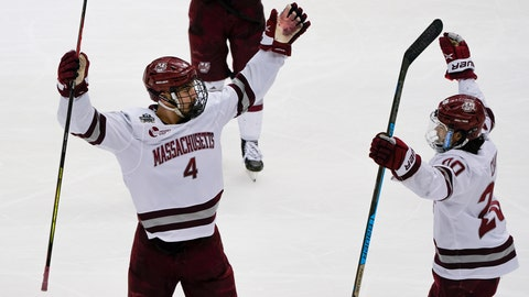 Massachusetts's Matthew Kessel (4) celebrates with Oliver Chau (20) after scoring against St. Cloud State during the first period of the NCAA men's Frozen Four hockey championship game in Pittsburgh, Saturday, April 10, 2021. (AP Photo/Keith Srakocic)