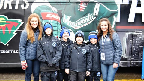 Jennifer & Angie hang out with members of a Tartan youth hockey team in front of the FOX Sports North Fan Express bus.