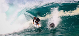 Australian surfer rides wave with hot-dogging dolphin