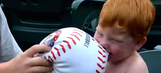 Shirtless little fan has the best time chewing on a toy baseball