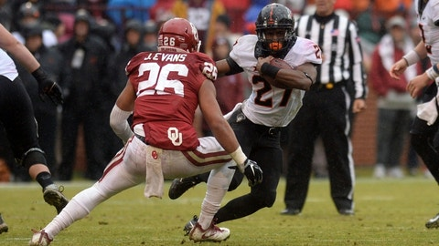 Dec 3, 2016; Norman, OK, USA; Oklahoma State Cowboys running back Justice Hill (27) attempts to elude Oklahoma Sooners linebacker Jordan Evans (26) during the fourth quarter at Gaylord Family - Oklahoma Memorial Stadium. Mandatory Credit: Mark D. Smith-USA TODAY Sports