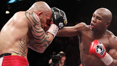 Floyd Mayweather Jr., right, lands a punch