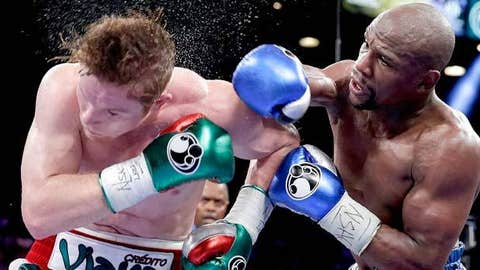 Image: (From left) Canelo Alvarez punched by Floyd Mayweather Jr. (© Eric Jamison / AP Photo)