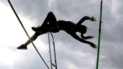 A high school student pole vaults as storm clouds hang