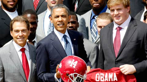 President Barack Obama is presented with a team helmet and jersey