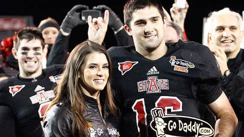 Arkansas State Red Wolves quarterback Ryan Aplin (16) is handed the most valuable player trophy by Danica Patrick