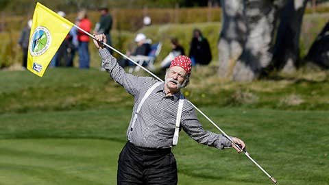 Actor Bill Murray stretches with the flagstick on the fifth green of the Pebble Beach Golf Links