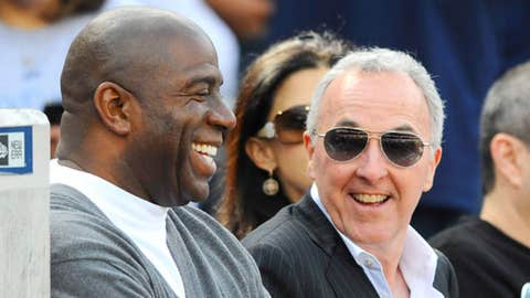 Magic Johnson sits with outgoing owner Frank McCourt