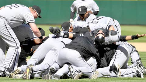 Chicago White Sox starting pitcher Philip Humber is mobbed by his teammates