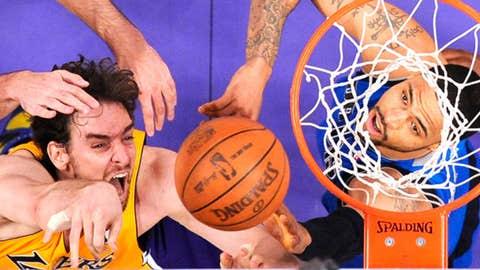 Los Angeles Lakers forward Pau Gasol, center, of Spain, puts up a shot as Dallas Mavericks forward Peja Stojakovic, left, of Serbia, and center Tyson