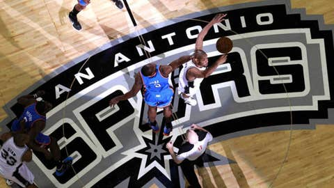 Tim Duncan #21 of the San Antonio Spurs and Serge Ibaka #9 of the Oklahoma City Thunder