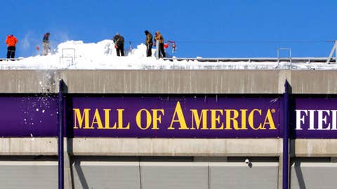 Workers shovel snow off the roof of Mall of America Field