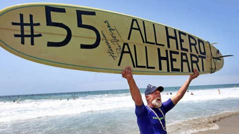 "Fred Hodges shows a surfboard he decorated during a ""paddle-out"" in honor of NFL star Junior Seau"