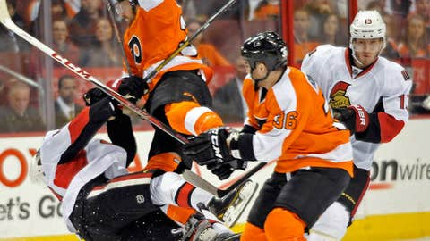 Flyers' Harry Zolnierczyk, center, collides with Ottawa Sentors' Mike Lundin