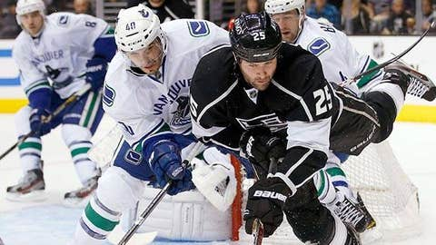 Vancouver Canucks' Maxim Lapierre, left, collides with Los Angeles Kings' Dustin Penner
