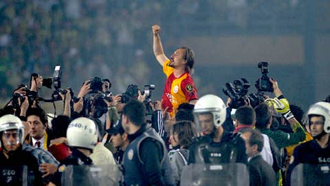 Galatasaray's Ayhan Amman celebrates surrounded by journalists and police officers