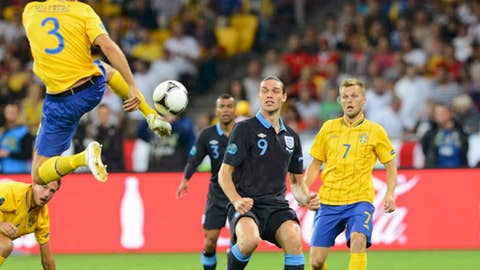 England's Andy Carroll watches Sweden's Olof Mellberg