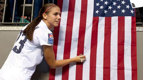 Alex Morgan #13 of the United States signs an autograph