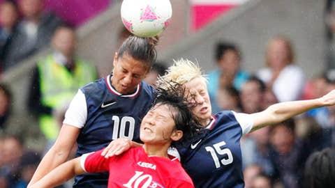 North Korea's Yun Hyon-hui (C) is challenged by Megan Rapinoe (R) and Carli Lloyd of the U.S.
