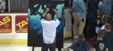 Watch man sing national anthem while painting canvas during hockey game