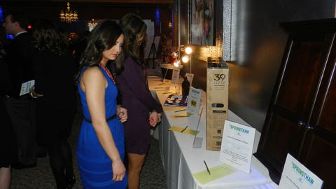 Angie and Kaylin check out the silent auction items, which included airline and vacation vouchers, interior design consultations, personal training packages and much more!